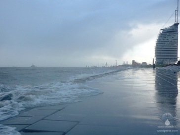 Die Brandung der Nordsee erreicht den Fuß des Weserdeiches am Sail City Hotel.