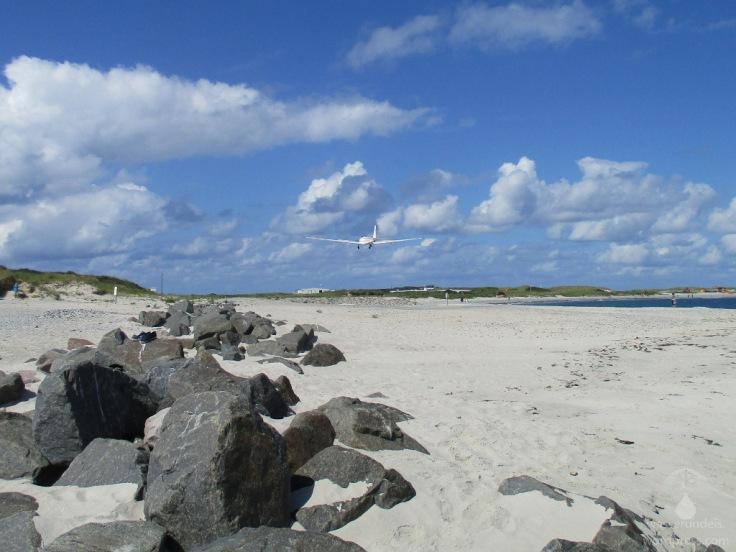 Tief fliegendes Flugzeug in niedriger Höhe über dem Strand der Helgoländer Düne.