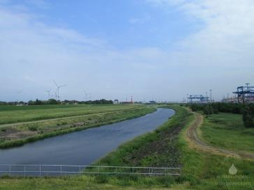 Blick vom neuen Seedeich, links Weddewarden und der alte Deich, rechts der Containerhafen.