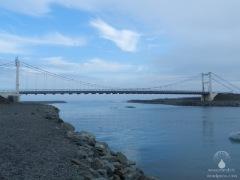 Brücke über den Jökulsá á Breiðamerkursandi, dahinter der Atlantische Ozean.