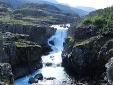 Der Wasserfall Sveinsstekksfoss am Berufjord inmitten von Basaltformationen.