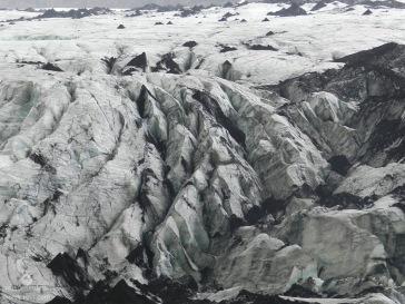 Gletscherspalten und Ascheablagerungen in der Zunge des Sólheimajökull.