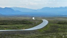 Weite Landschaften im Suðurland, im Südwesten der Insel. Island haut uns von der ersten Sekunde an vom Hocker. Auch Straßen werden zunehmend fotogen, wie hier der Þingvallavegurm, eine der wichtigsten Straßen der Insel. Link im Hintergrund erhebt sich der mächtige Schildvulkan Skjaldbreiður.